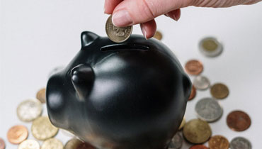Coin being inserted into black piggy bank