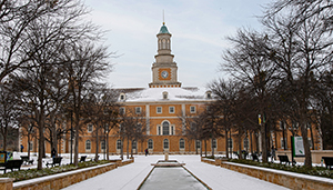 snow covered hurley building and the library mall on campus