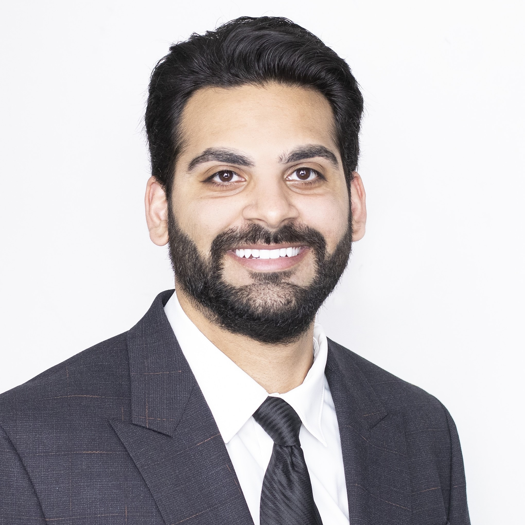 Ahmed smiling in suit with white background