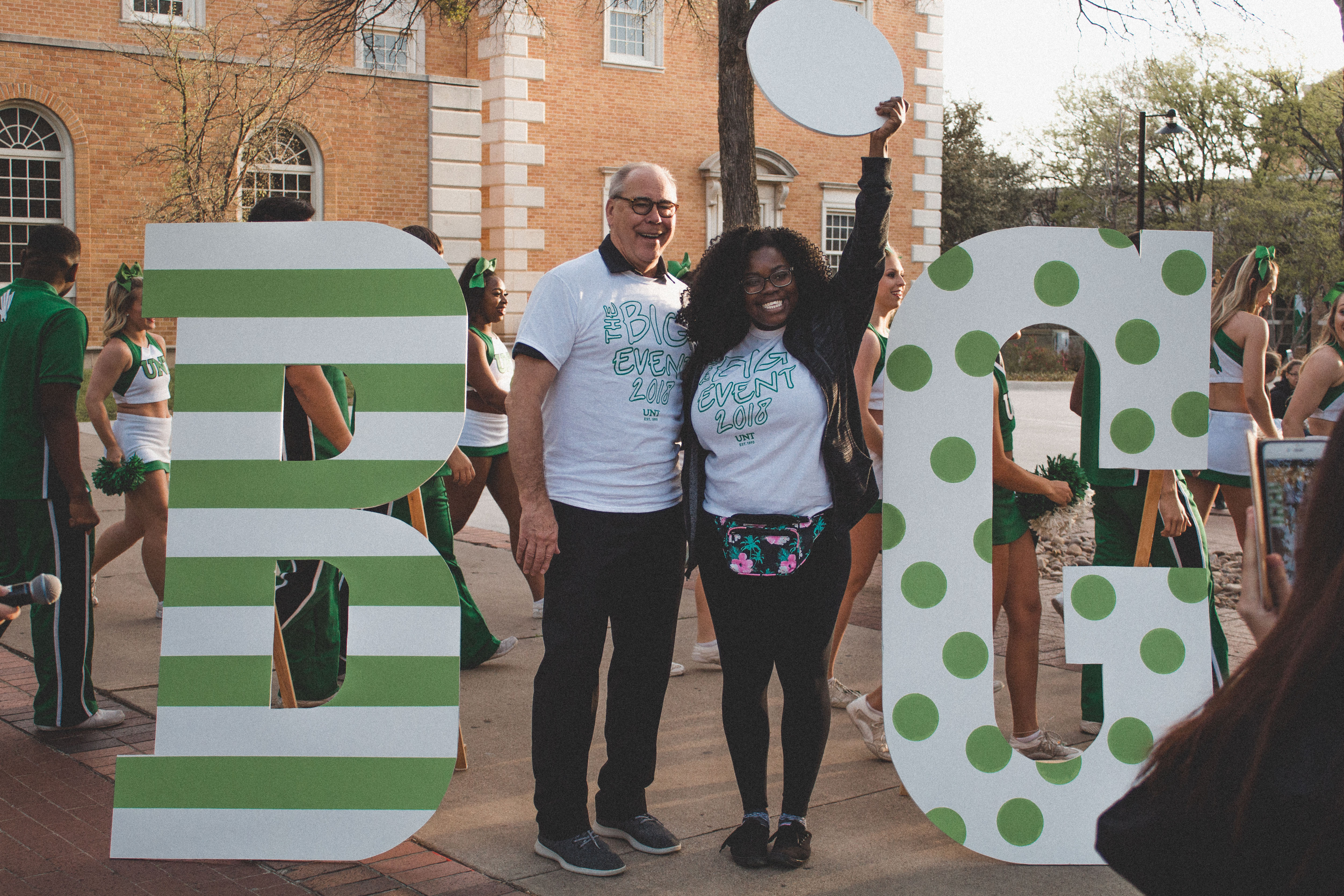 "Student and UNT President standing with a sign that says ""Big"""