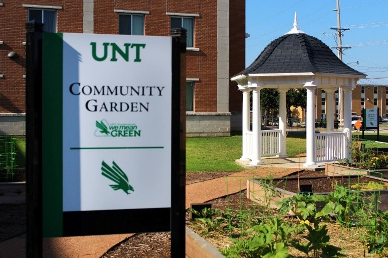 Sign of UNT Community Garden in front of the gazebo in the garden