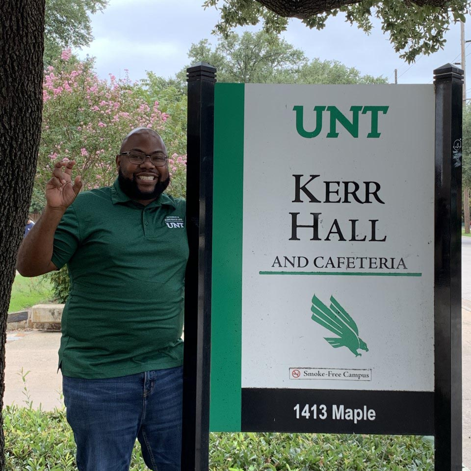 Russell in front of the Kerr Hall sign