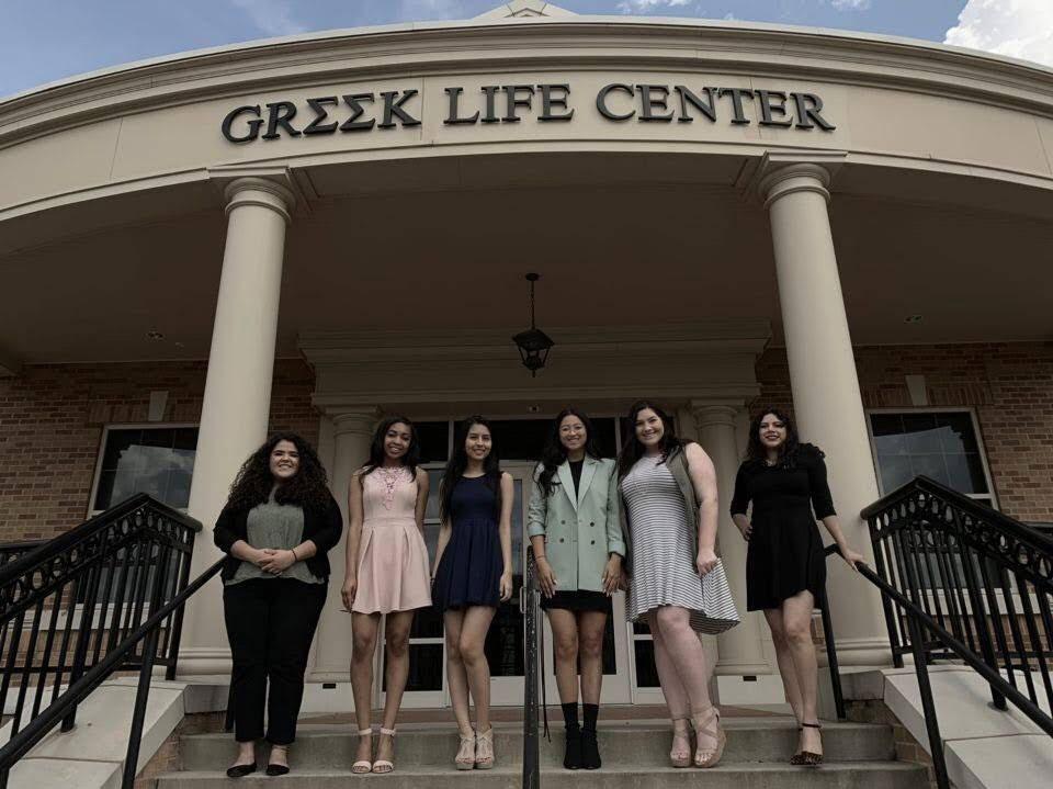 Sorority women standing in front of the greek life center
