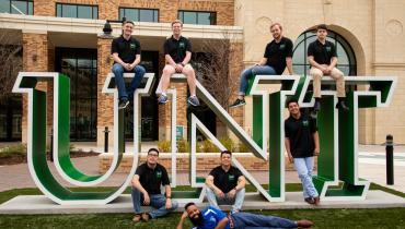 "Fraternity men posed next to the ""unt"" letters at the welcome center"