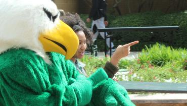 Student talking to UNT's eagle mascot