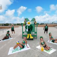 North Texas Cheer COED posed in front of the Mean Green chair at the Apogee stadium
