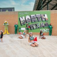 North Texas COED with Santa hats in front of The North Texas painting at Apogee stadium