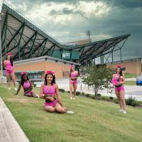 North Texas All-girls group in pink uniform in front of Apogee stadium