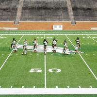 North Texas All-girls group on the football field in Apogee stadium