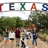 Students Smiling Under Texas Sign