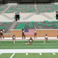 North Texas All-girls holding American Flag on Apogee's football field