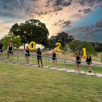 North Texas All-girls in black dresses holding balloons that spell out 2021