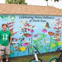 Thomas next to mural