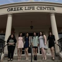 Sorority women standing in front of the greek life center