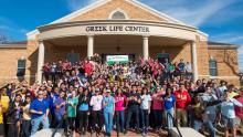 Greek students in front of center for fraternity and sorority life building