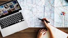 laptop, map and hand with pen
