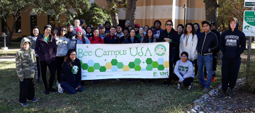 students holding bee campus usa sign