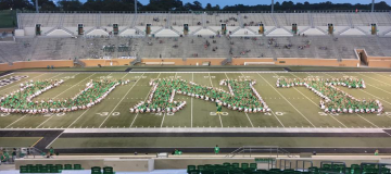 students creating letters UNT on football field