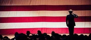 Man standing on a stage with american flag background