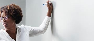 Person writing on whiteboard