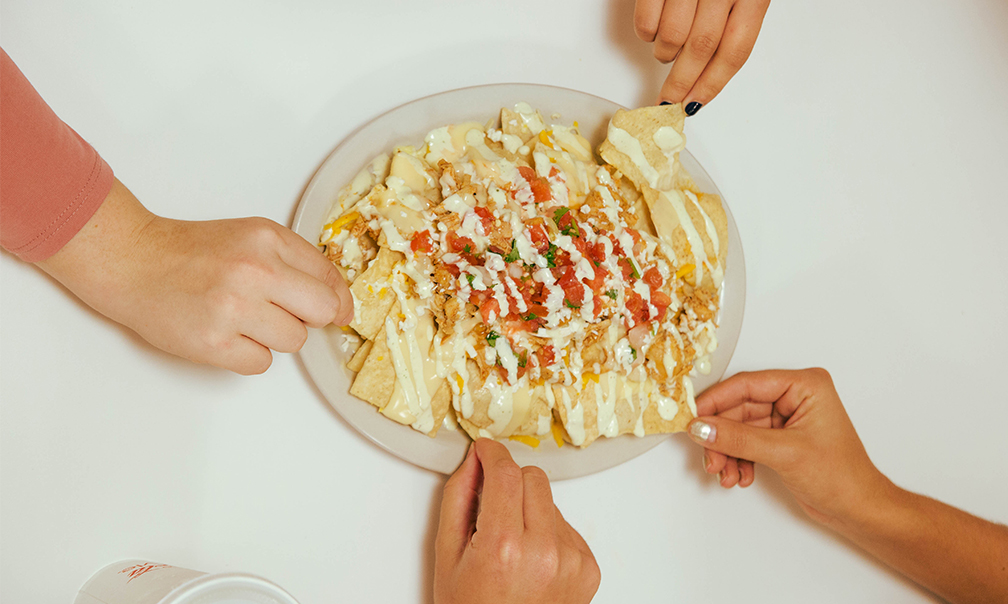 image of people reaching for a plate of nachos